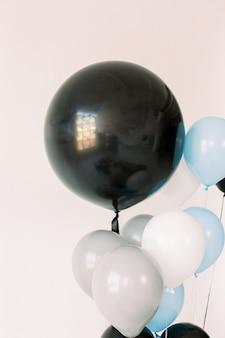 Palloncini neri, grigi, blu e bianchi su sfondo bianco. concetto di celebrazione. mongolfiere per una vacanza, festa di compleanno. foto per poster o cartoline.