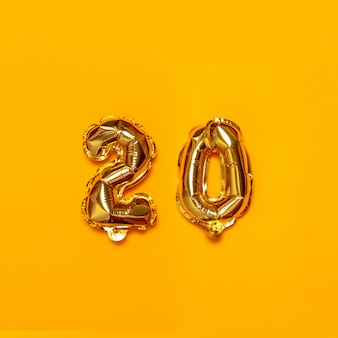 Palloncini numerati in oro bianco elio con decorazione di festa 20 su una superficie gialla. concetto di seguaci di congratulazioni.