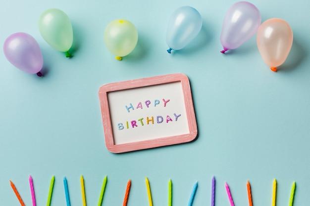 Palloncini sopra la cornice di buon compleanno con candele colorate su sfondo blu