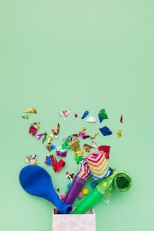 Palloncino blu; coriandoli e trombe che escono dalla scatola su sfondo verde