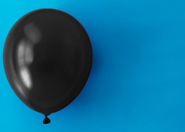 Palloncino nero su sfondo blu con spazio di copia