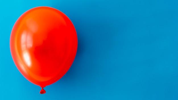 Palloncino rosso su sfondo blu con spazio di copia
