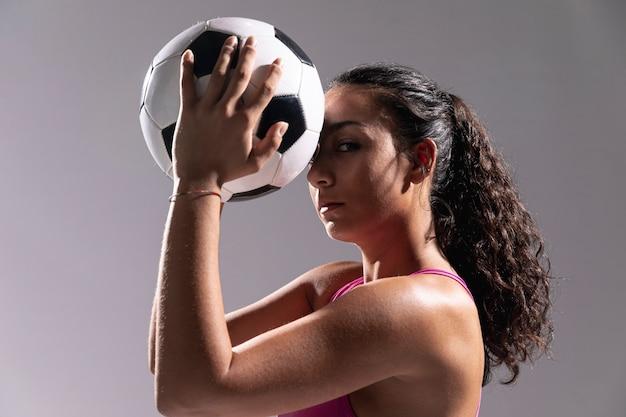 Pallone da calcio adatto della tenuta della donna del primo piano