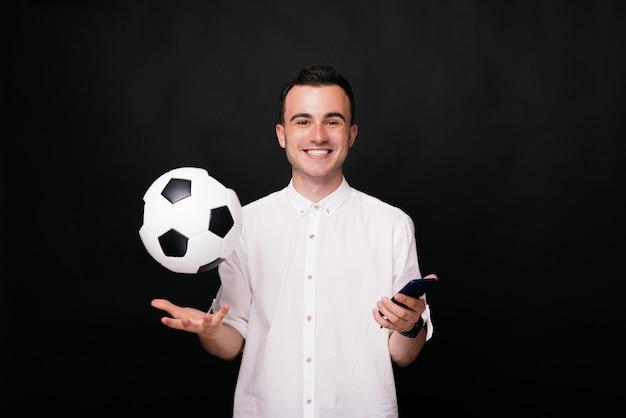 Pallone da calcio che levita nella mano di un giovane ragazzo sorridente, che tiene anche il suo smartphone. palla in aria.