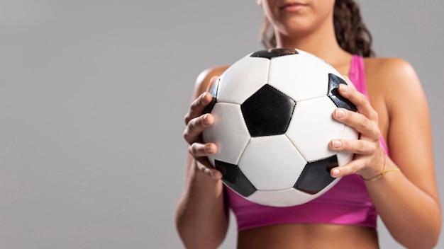 Pallone da calcio della tenuta della donna del primo piano
