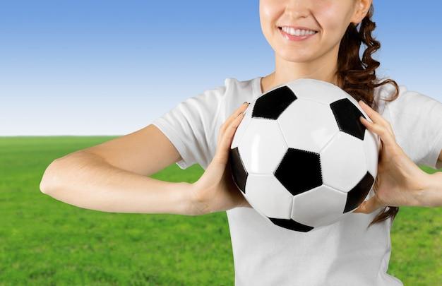 Pallone da calcio della tenuta della giovane donna sulla sua mano