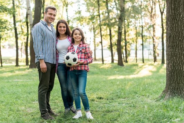 Pallone da calcio della tenuta della ragazza che sta con il suo genitore in parco