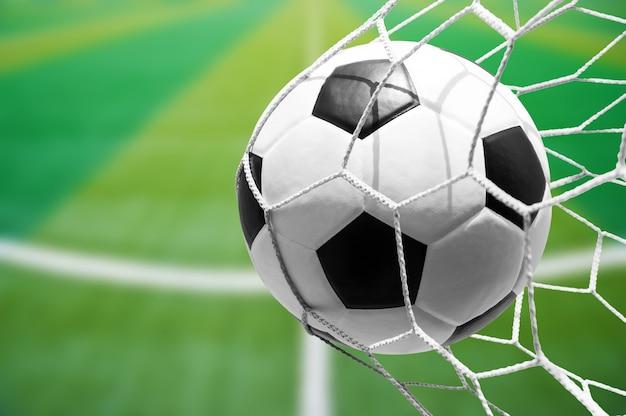 Pallone da calcio in rete con sfondo del campo di calcio