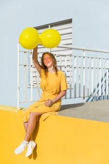 Palloni della tenuta della donna della foto a figura intera