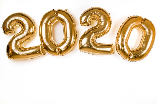 Palloni dorati del nuovo anno 2020 isolati sopra la parete bianca