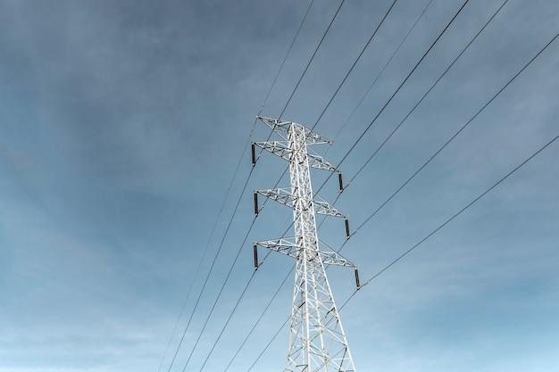Palo di elettricità contro le nuvole del cielo blu, linea di trasmissione di elettricità a rurale, palo di elettricità ad alta tensione sul fondo luminoso delle nuvole del cielo, pilone della trasmissione di elettricità