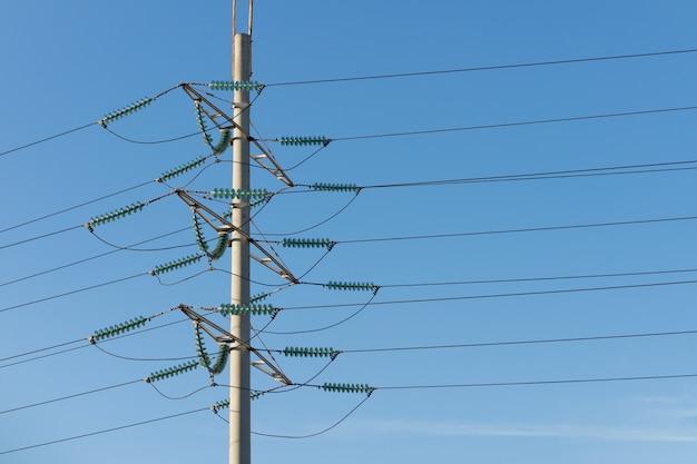 Palo di potenza ad alta tensione contro il cielo blu