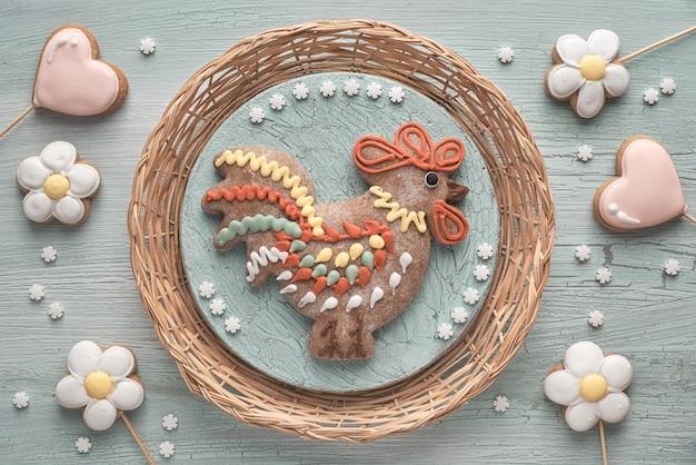 Pan di zenzero a forma di uccello gallo, fiori e cuori su legno testurizzato.