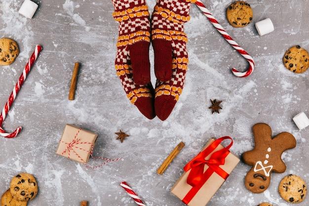 Pan di zenzero, biscotti, marshmallows, ciambelline bianche rosse, cannella, altre spezie, scatola regalo si trovano intorno a guanti caldi