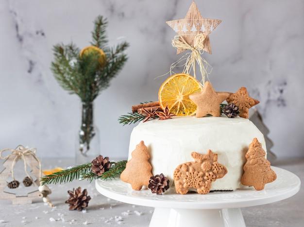 Pan di zenzero di natale o capodanno addobbato con biscotti di pan di zenzero, rami di abete, coni, spezie e fetta d'arancia essiccata.