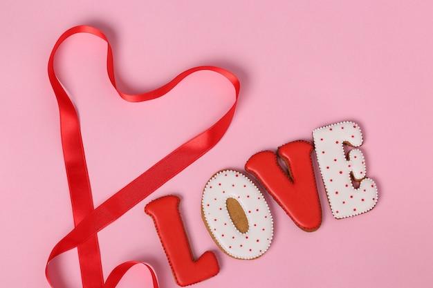 Pan di zenzero fatti in casa con lettere amore per san valentino situato su uno sfondo rosa, vista dall'alto