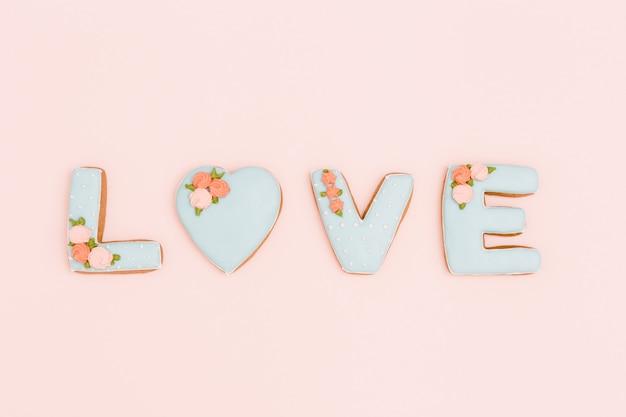 Pan di zenzero fatti in casa con lettere amore su sfondo di rosa pastello. composizione di san valentino o cartolina d'auguri con lo spazio della copia per testo o congratulazioni. stile minimal.