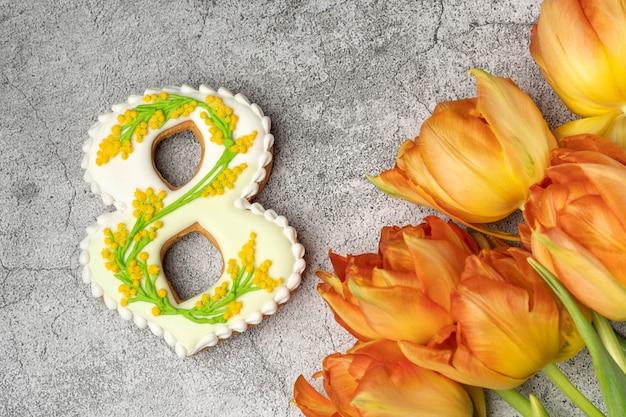 Pan di zenzero fatto a mano sotto forma di numeri otto su un tavolo grigio cemento e tulipani arancioni, regalo per la giornata internazionale della donna