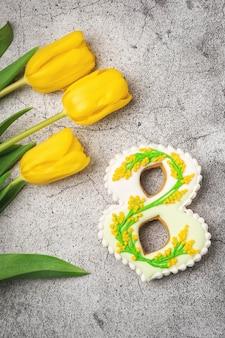 Pan di zenzero fatto a mano sotto forma di numeri otto su un tavolo grigio cemento e tulipani gialli, regalo per la giornata internazionale della donna