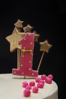 Pan di zenzero rosa con il numero 1 su una torta di festa su un buio