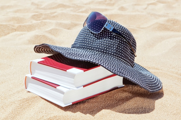 Panama per il sole con libri da leggere sulla spiaggia. occhiali da sole.