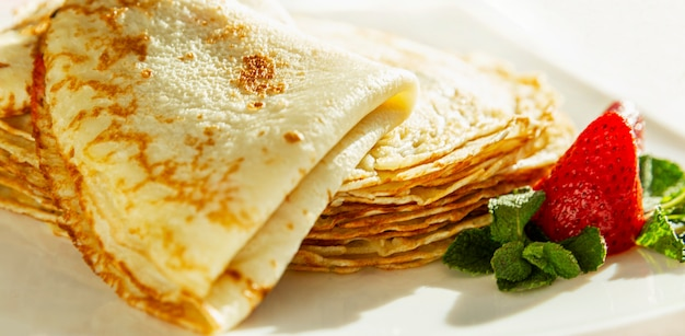 Pancake appetitosi con fragole e foglie di menta su un piatto. piatto tradizionale per le vacanze di carnevale. avvicinamento. panorama.
