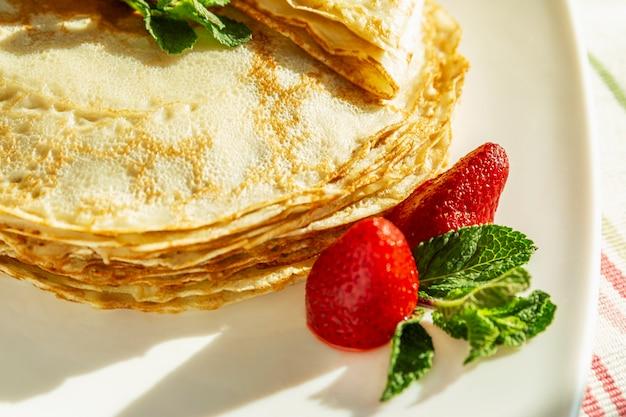 Pancake appetitosi con fragole e foglie di menta su un piatto. piatto tradizionale per le vacanze di carnevale. avvicinamento.