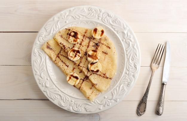 Pancake con banana e cioccolato su un piatto