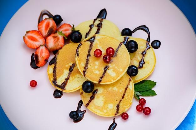 Pancake con frutti di bosco e cioccolato dopante sul piatto rosa