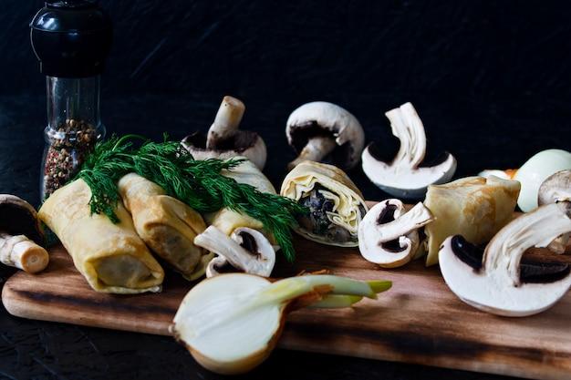 Pancake con funghi su una tavola di legno su uno sfondo nero.