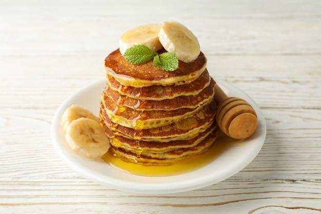 Pancake con la banana e il miele sulla tavola di legno bianca