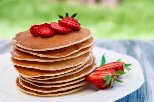 Pancake con la fragola e la menta fresche sul piatto bianco sul giardino di legno rosa o sulla natura. pila di pancake sul tavolo.