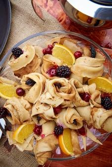 Pancake con le bacche fresche in un primo piano del piatto di vetro