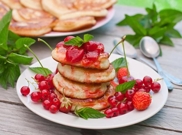 Pancake con le bacche su una tavola di legno in un giardino di estate