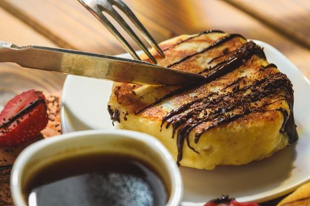 Pancake con le fragole cioccolato e caffè su una tavola di legno