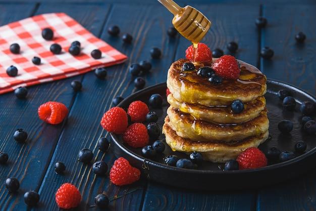 Pancake con miele e le bacche su una tavola di legno