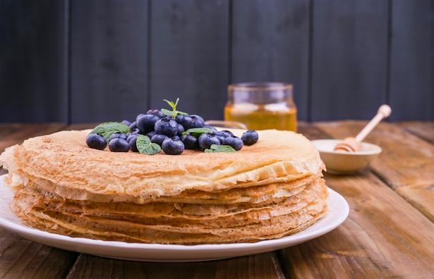 Pancake con mirtilli e miele su un piatto, sul tetto in legno. dolci tradizionali per la festa russa di maslenitsa. spazio libero per il testo. colpo del primo piano