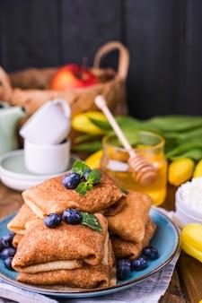 Pancake con mirtilli e miele su un piatto, sul tetto in legno