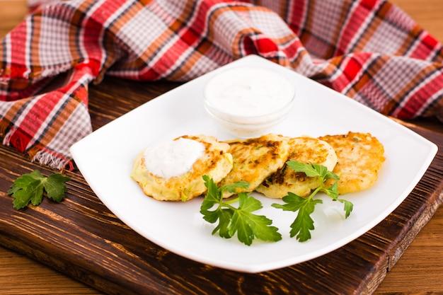 Pancake da una zucchina con salsa e l'erba sulla tavola di legno