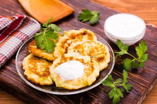 Pancake da una zucchina, salsa e prezzemolo sulla tavola di legno