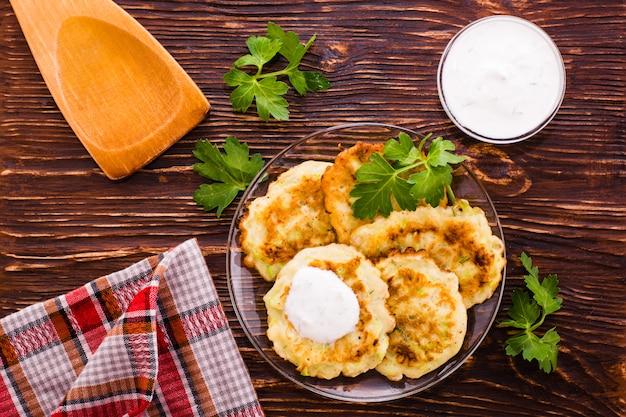 Pancake da uno zucchini, una salsa e un prezzemolo sulla tavola di legno, vista superiore