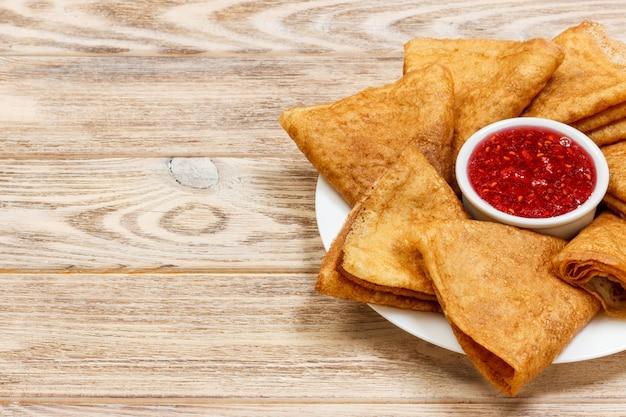 Pancake deliziosi con i lamponi sulla vista superiore del tavolo da cucina di legno con lo spazio della copia.