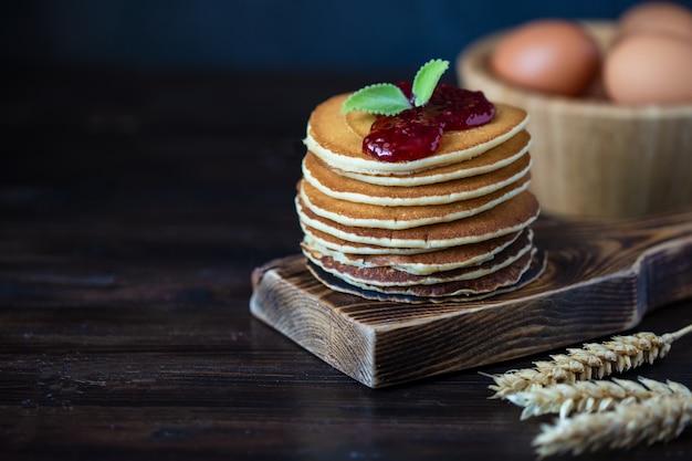Pancake deliziosi con inceppamento e la menta su una tavola di legno scura