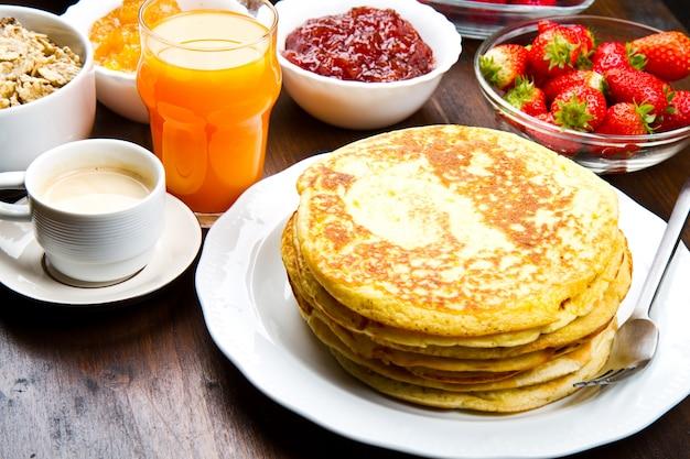 Pancake deliziosi sulla tavola di legno con i frutti