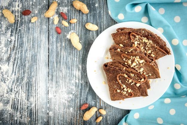 Pancake dell'avena del cioccolato con caramello e le noci sulla tavola di legno grigia.