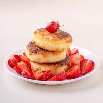 Pancake della ricotta con le fragole affettate sulla vista di angolo isolata piatto bianco