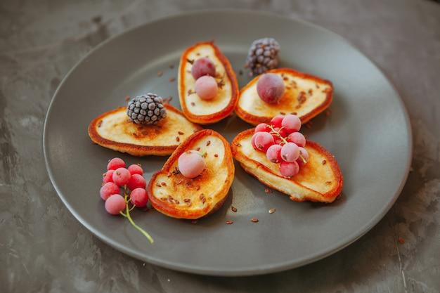 Pancake di vista dell'angolo alto in piatto con le more e i mirtilli rossi sulla tavola strutturata. orizzontale