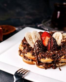 Pancake di vista frontale con i frutti sulla scrivania grigia