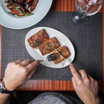 Pancake di vista laterale con carne con il coltello e la forcella e melanzana fritta e mano umana in piatto bianco sulla tavola di legno