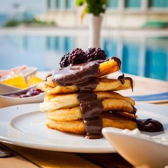Pancake di vista laterale con cioccolato e la mora su una tavola di legno contro la superficie dello stagno
